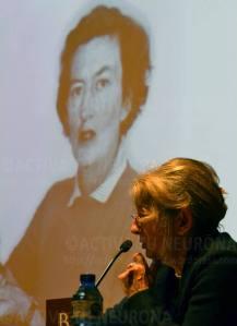 Mª José Casado en un momento de la conferencia. Mary Leakey al fondo. Credit: Izaskun Lekuona