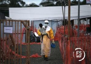 Un trabajador de MSF lleva en brazos a una niña, posible infectada de Ébola, en el centro de MSF de Paynesville, en Liberia. La niña y su madre, ambas con síntomas de la enfermedad, esperaban los resultados de la pruebas. Foto MSF: © John Moore/Getty Images